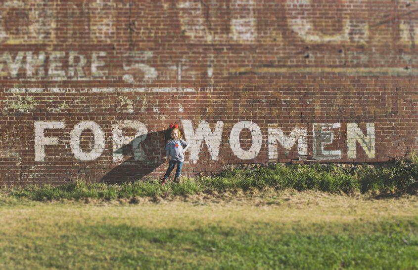 Mädchen vor einem großen Graffiti, auf dem steht: FOR WOMEN